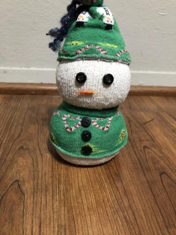 Step 11: Take a toothpick and color the pointy end of it orange, then cut the toothpick so you only have the colored end. Glue the toothpick onto the head of the snowman.  Step 12: Enjoy your cute sock snowman, use it as a decoration for yourself or gift it to a friend or loved one!